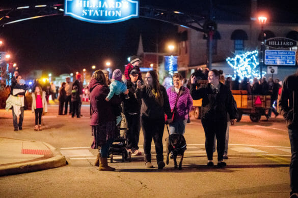 People walking around with dog at Tree Lighting event