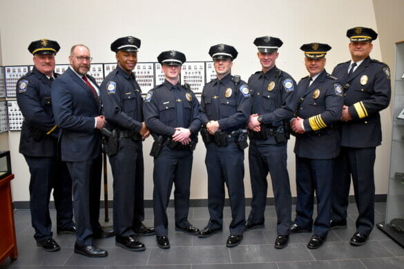 New police officers standing with Chief Fischer, Deputy Chief Grille, and Safety Director Mossic.