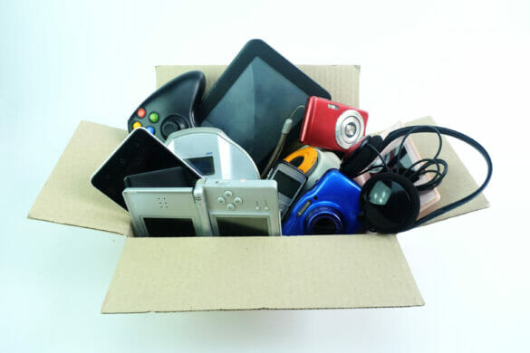 A box to be recycled, filled with various electronics, including handle held games, cameras, phones, and headphones.