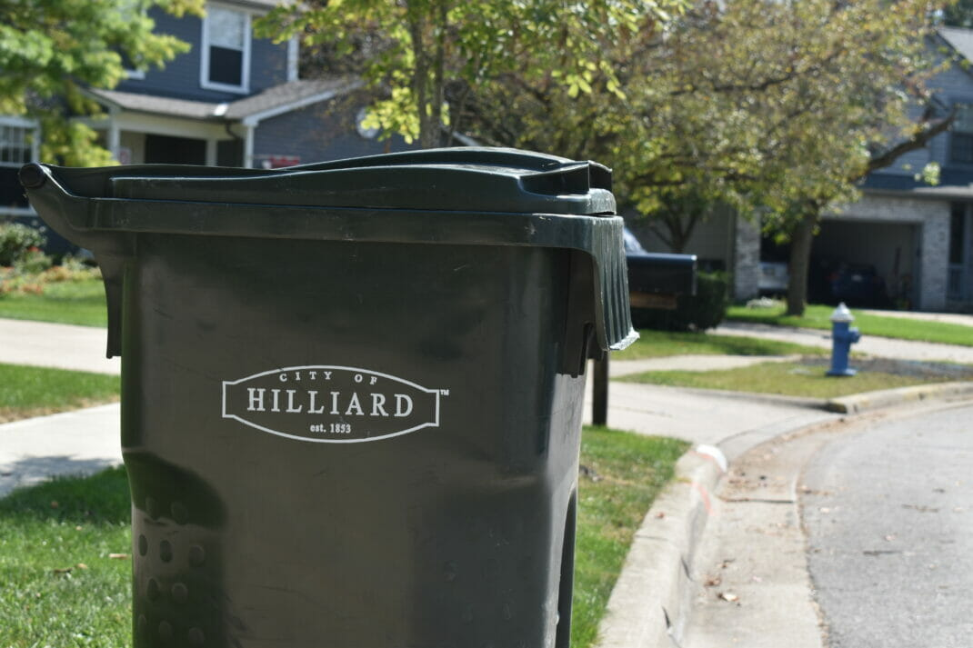 A close up shot of a black trashcan in front of houses