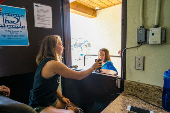 Girl at front desk of phone scanning childs key fob