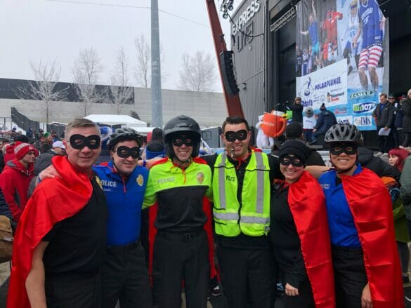 Police officers dressed in masks and red capes for Special Olympics
