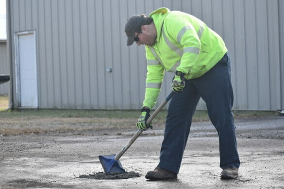 Service worker stamping down pot hole