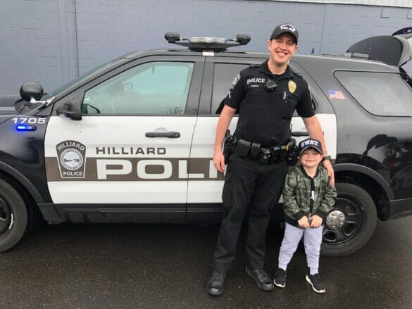 Maxwell with Officer Agosta in front of the police car