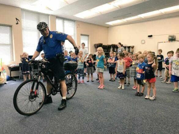 Officer demonstrating bike safety to kids