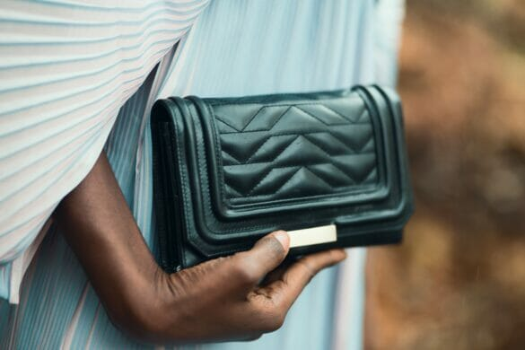 Woman holding black clutch