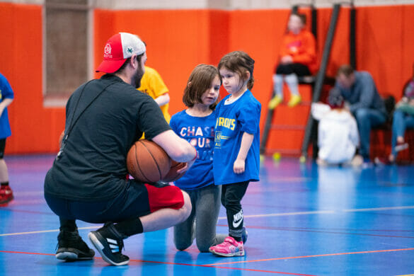 Little girl working with coach to learn basketball