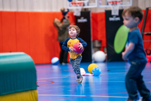 Little boy playing with a basketball in a the community center gym during Tyke Time