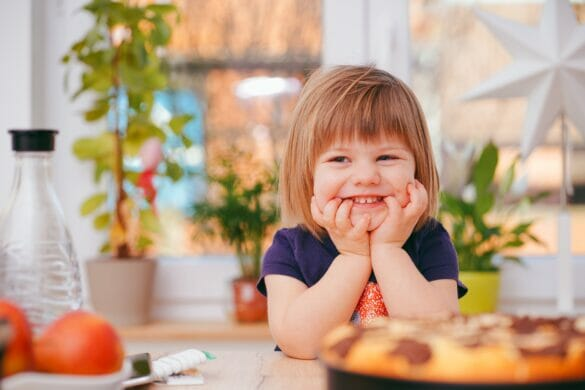 Little girl sitting at table with food in front of her