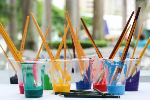 Cups filled with paint and pencils