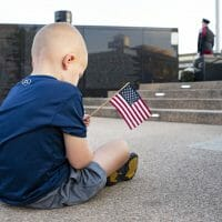 a little boy holding a flag while sitting on the ground at first responders park