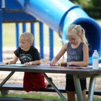 A boy and girl coloring at a picnic table