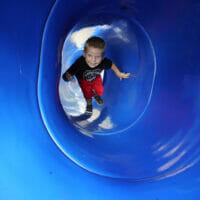A boy climbing up a blue slide