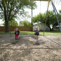 A boy and girl swinging