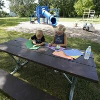 a boy and girl coloring at picnic table