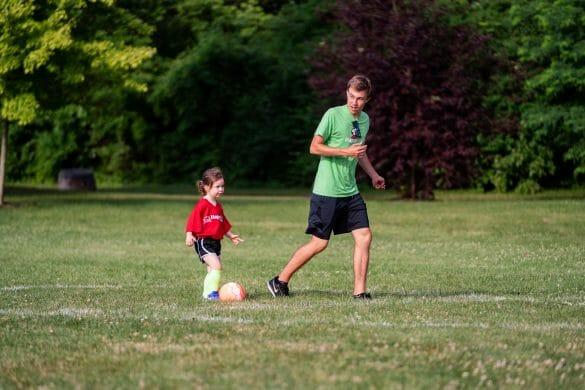 Man coaching little girl to kick soccer ball