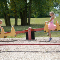 A boy and girl on a seesaw