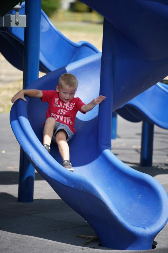 A boy sliding down a blue slide