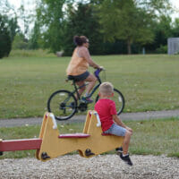 A boy on a seesaw watching a woman bike by