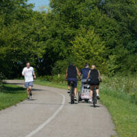 People riding their bikes and jogging on a trail