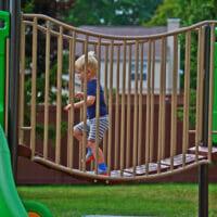 A boy running across bridge of playground