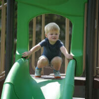 A little boy on green slide