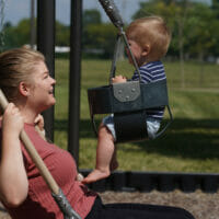 A mom on joint swing with son