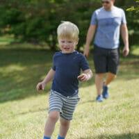 A little boy running across the grass, father behind him