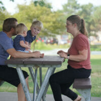 A family sitting picnic table