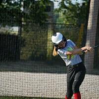 A girl swinging a bat
