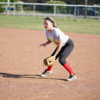 A girl in ball field waiting to catch ball