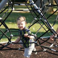 A boy playing in a jungle gym