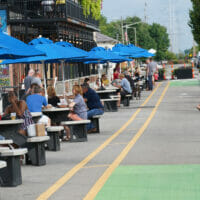 People eating at tables outside at Crooked Can