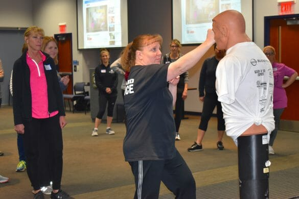 officer demonstrating self-defense to women