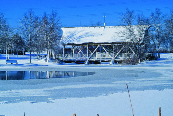 Snow covered lake and bridge at Homestead park in winter.