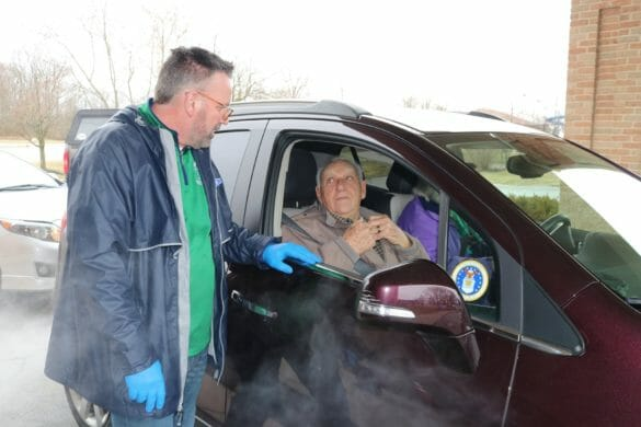 Dave Judson handing food to a senior citizen in the drive through