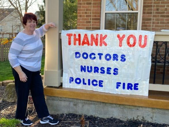 Woman standing next to sign thanking first responders