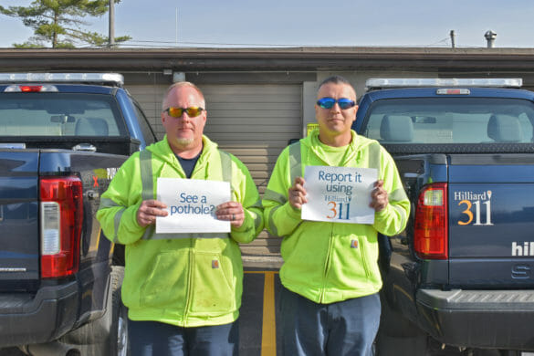 "Public service workers holding up signs saying ""See a pothole? Report it using Hilliard 311""."