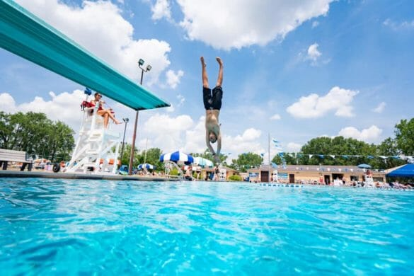 Boy diving into pool from diving board