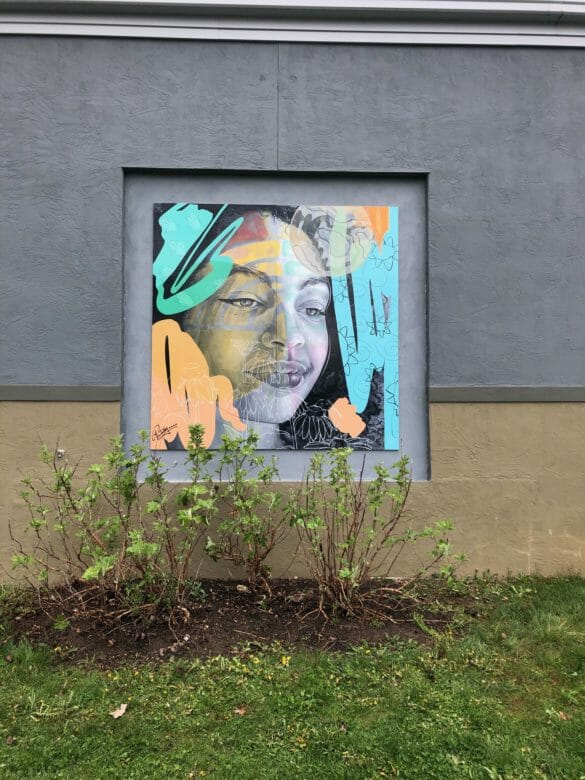 A mural on the side of a building of a girl with colors and doodles around her.