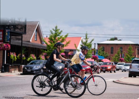 An elderly couple riding their bikes downtown