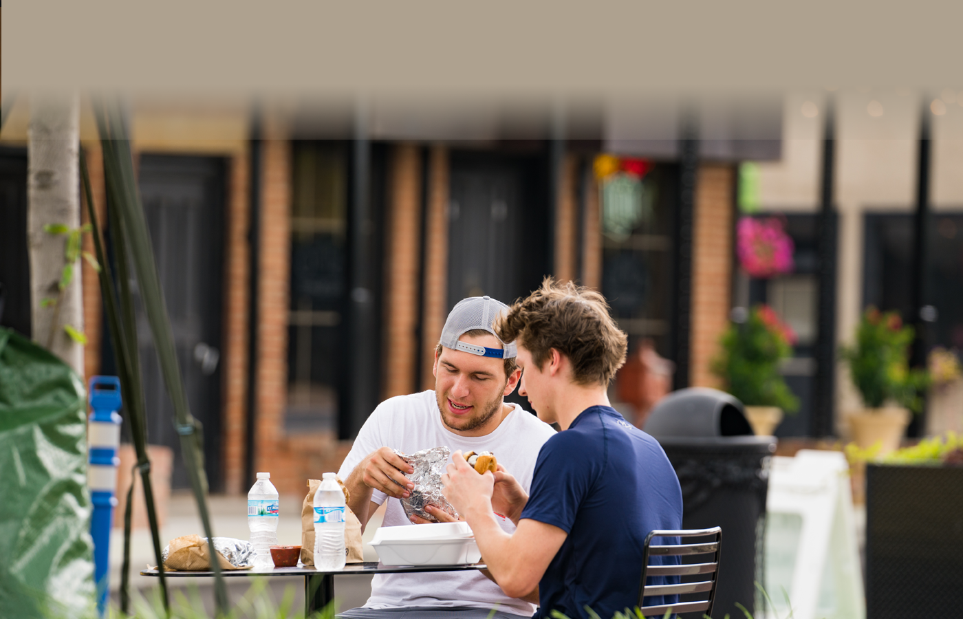 two men eating food outside