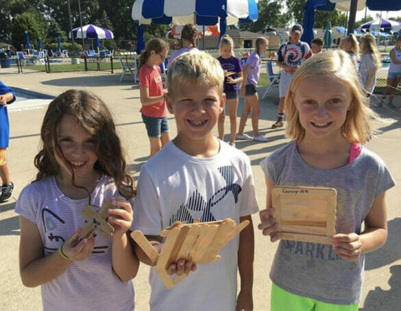 Three kids holding up boats made from popsicle sticks