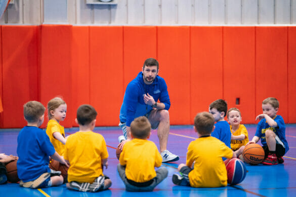 A coach talking to a group of young kids playing basketball