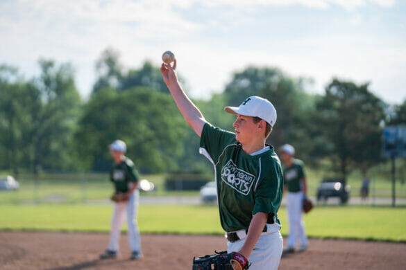A boy holding a baseball up