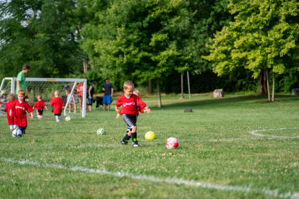 A little boy kicking a soccer ball while kids play soccer in the background