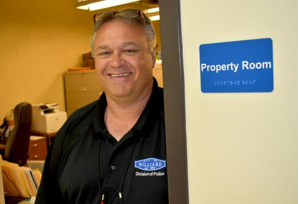 Todd Harper standing in doorway smiling, next to Property Room sign