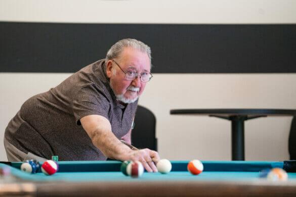 An older man playing pool