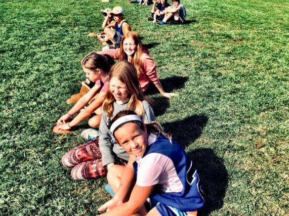 A group of girls lined up, sitting on grass