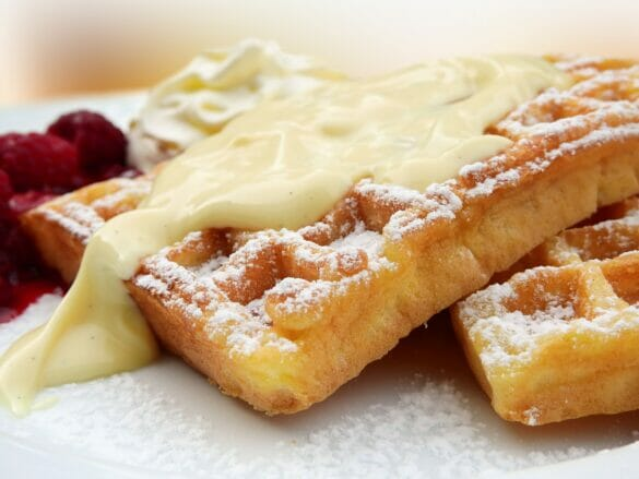 A closeup of waffles with cream, powder sugar, and fruit on them